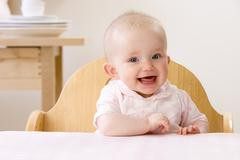 happy baby girl sitting in high chair - stock photo