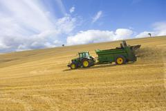 Tractor spreading fertilizer in sunny rural field Stock Photos