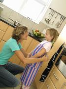 Mother and daughter (6-8) standing in kitchen, girl wearing striped apron, wo Stock Photos