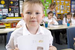 school boy displaying artwork in classroom - stock photo