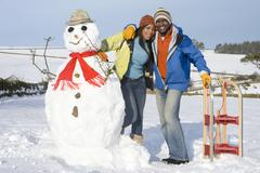 couple with snowman and sled in snowy field - stock photo