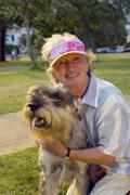 Stock Photo of senior woman in visor lifting dog