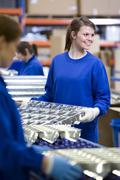 smiling worker moving aluminium light fittings in factory - stock photo