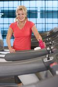 Portrait of smiling senior woman with water bottle on treadmill in health clu Stock Photos
