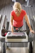 Senior woman programming treadmill in health club Stock Photos