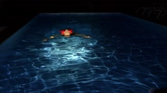 Young Woman Swims in the Pool on her Back at Night. Slow Motion. Stock Footage