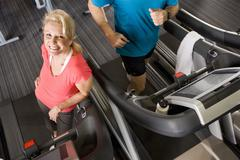 Portrait of smiling senior woman leaning on treadmill in health club Stock Photos