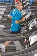 man listening to music on headphones and running on treadmill in health club - stock photo