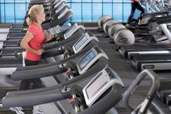 Senior woman running on treadmill in health club Stock Photos