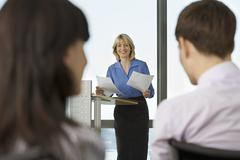 businesswoman standing behind lectern, giving presentation to colleagues, foc - stock photo