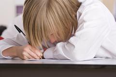 school boy taking test on desk in classroom - stock photo