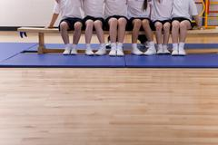 School children sitting on bench in school gymnasium Stock Photos