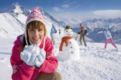 Family building snowman together and having snowball fight Kuvituskuvat
