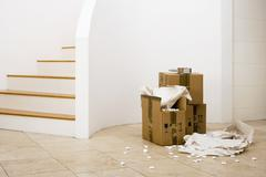small stack of boxes, paper and packing foam beside staircase in sparse room - stock photo
