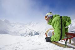 Smiling man with sled on mountain top Stock Photos