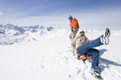 Man puling wife through snow on sled Stock Photos