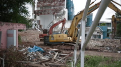 Tracking wide shot of excavator in action with foreground plants Stock Footage
