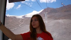Young girl climbs a cable car to the foot of Mount Elbrus and photographs Stock Footage