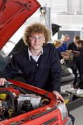 student repairing car in automotive vocational school - stock photo