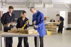 teacher teaching students bricklaying in vocational school - stock photo