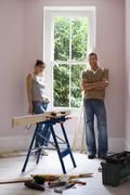 Couple doing diy at home, woman holding glue gun beside timber on workbench,  Stock Photos