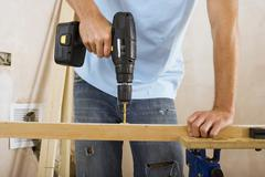 Man doing diy at home, drilling hole in piece of timber on workbench, front v Stock Photos