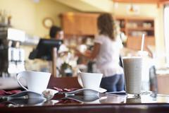 Waitress serving female customer in cafe, focus on glass and coffee cups on t Stock Photos