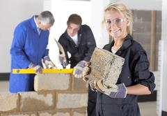 teacher talking to student using level in bricklaying vocational school - stock photo
