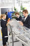 students constructing electric vehicle prototype in vocational school - stock photo