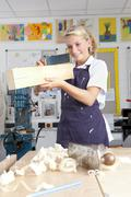 Smiling student measuring planed wood in vocational school Stock Photos