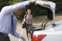Man opening car boot in car park, focus on businesswoman walking with luggage Stock Photos