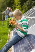 Boy holding bunch of carrots near large solar panels with family in backgroun Stock Photos