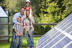 Happy family standing near large solar panels Kuvituskuvat