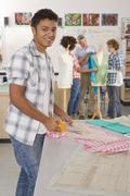 Smiling student cutting fabric in home economics classroom Stock Photos