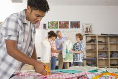 Stock Photo of serious student cutting fabric in home economics classroom
