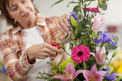 Smiling woman trimming flowers in floral arrangement in classroom Stock Photos