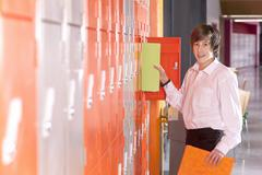 Student removing binder from school locker Stock Photos