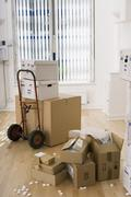 Large cardboard box on hand truck in office, small boxes on wooden floor near Stock Photos