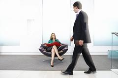 Businessman walking past businesswoman sitting in chair in office lobby (blur Stock Photos