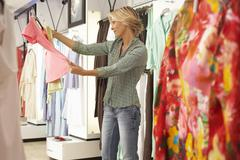 Mature blonde woman shopping in clothes shop, choosing between two different  Stock Photos