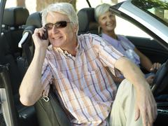 senior couple sitting in convertible car, man in sunglasses using mobile phon - stock photo