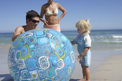 two generation family playing with large turquoise beach ball, sea in backgro - stock photo