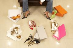Woman trying on different pairs of high heels in shoe shop, low section, elev Stock Photos