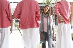 woman window shopping, looking at three mannequins wearing pink tops and whit - stock photo