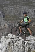 Male mountain biker sitting on bicycle at edge of rock, looking at view, side Stock Photos