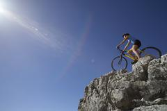 female mountain biker sitting on bicycle at edge of rock in sunlight, low ang - stock photo