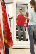 Woman trying on red top in clothes shop, looking at reflection in mirror, smi Kuvituskuvat