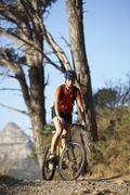 female mountain biker cycling along tree-lined mountain path, portrait - stock photo