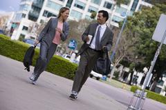 businessman and businesswoman walking on pavement in city, carrying rucksacks - stock photo