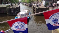 Canal cruise in Amsterdam with Onze hollandse nieuwe flags in The Netherlands Stock Footage